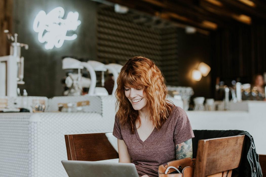 Mujer disfrutando de su portátil nuevo conseguido por renting tecnológico.